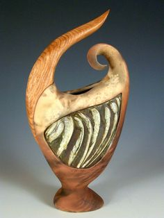 Early Sprout by Jan Jacque. The feeling of new growth is intrinsic in this sculpted clay and cherry wood piece. The vessel is slab built construction and fired multiple times to achieve the rich surface. A carved piece of wood is incorporated into the ceramic form. Each piece is unique. Slight variations in the wood and patterning may occur. Dimensions: 15″H, 8″W, 4″D  $360
