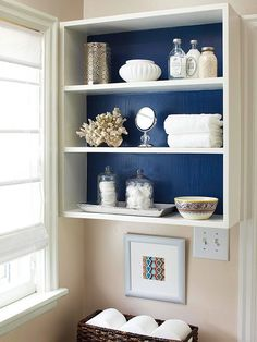 Add colorful contrast to basic white cabinets by wallpapering their back walls. The process is simpleall you need is prepasted wallpaper measuring tape and a few other DIY supplies. - Over the Toilet Storage - Ideas of Over the Toilet Storage Navy Blue Bathroom Decor, Navy Blue Bathrooms, Nautical Bathrooms, Beach Bathrooms, Small Bathrooms, Brown Bathroom, Small Kitchens, Small Bathroom Storage, Bath Storage