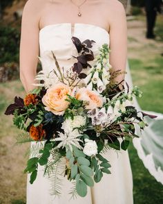 Elizabeth Lewis of The Nouveau Romantics designed all of the floral elements, including the bride's oversized clutch of foxglove, plum foliage, astilbe, umbrella ferns, geranium leaves, thistle, ranunculus, caramel Antike garden roses, white dahlias, and sea grass.