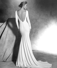 IVANIA style: Simple mermaid wedding dress in crepe. Bodice with long sleeves and covered buttons at the cuffs. Plunging V back and covered buttons.