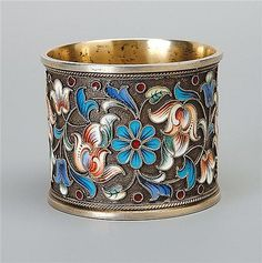 A Russian silver gilt and cloisonne enamel napkin ring, makers mark T.K Moscow 1899-1908  the sides with shaded polychrome trailing flowers and leaves to stipled ground, 84 standard 4 cm high