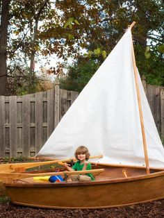 Child in Brown and White Sandbox Sailboat