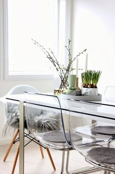 Light and airy Scandinavian kitchen with a little fresh spring decor. I'm almost certain those glass chairs are Ikea's Tobias chairs. The Eames chair, with its wood legs and shaggy fur throw, brings a soft, natural touch that offsets the modern industrial feel of the glass and chrome so the room doesn't end up looking too cold.