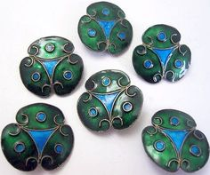 A set of six Arts & Crafts enamel buttons, circa 1900.  Each trefoil shaped button is inlaid with blue and green enamel, the reverse in green enamel, mounted in silver, diameter of each 25mm