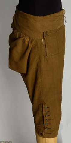 "MIDDLE CLASS MAN'S DAY SUIT, RHODE ISLAND, 1780s  Go Back Lot: 194 November 13, 2013 - NYC New York City Brown linen suit dyed w/ butternuts: 1 unlined jacket w/ self fabric buttons, 10 front & 2 back, 2 pockets w/ flaps, Ch 36"", L 43""; 1 pair matching breeches lined w/ natural linen, waist band laces CB, 6 brass knee buttons, W 30""-32"", Inseam 17"", (knee bands' original buckles missing & replaced w/ buttons, scattered fade spots on coat & breeches) excellent. Provenance: Mason family…"