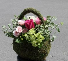 Feminine floral design in a purse made of moss - by Martin's the Flower People