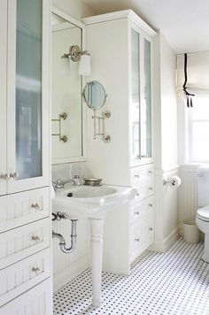 All white done right — beautiful vintage style bathroom with lots of subtle detailing. Love those double built-ins, the basketweave tile with black pegs (what is better? nothing.) and the black ribbon on that soft balloon shade.