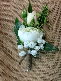 Sweet little boutonnière with white ranunculus ,spray rose,babies breath and ivy all wrapped in jute