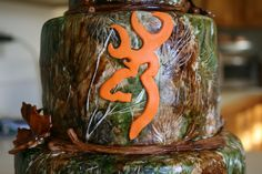"""Hunter's Birthday Cake - The customer ordered this 3-tiered, fondant covered cake for her husband's birthday.  He is a hunter so she wanted to incorporate the """"real tree"""" camo with the Browning logo in Hunter Orange.  I hand painted the entire cake and did """"twigs"""" as the border for each tier."""
