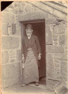 A full length photograph of an unknown man with a beard and bowler hat, outside the outside building at Penlee. He wears a suit and worker's apron, holding a trowel, which suggests he was a gardener. - Collections - Penlee House Gallery and Museum Penzance Cornwall UK