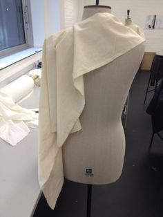 using one meter of calico to create shape and detail. then making a cut in the fabric and trying it on the stand