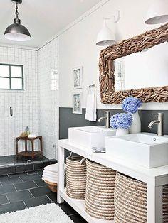 小枝を集めたような個性的なミラーフレームが目に留まる洗面所。洗面台の下に並んだ大きなバスケットがおしゃれな収納になっています。ホワイト×グレー×ブラウンという見事なカラーコーディネートです。
