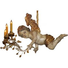 An Unusual 18th century 3-light Italian Winged Angel Chandelier  Italy  18th Century  A Whimsical 18th century Three-light Italian Polychrome and Parcel Gilt Angel Chandelier, pictured in flight and carrying a gilded flowering branch accented with glittering leaves, fruit, and berries, and fitted with three tole corona bobeches for candles, now electrified