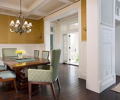 Unify with Trimwork The coffered ceiling, crown molding, and wall paneling used throughout this home's main level create visual harmony amongst the spaces. Changes in the color of the wall coverings lend separation between the entryway, dining room, and living room.