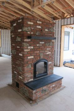 Finished Masonry Heater in Bend, OR. I like the simple design with the mantle and bench.  Still not keen on brick though.