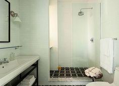 Wastafel over heel de breedte, staalonderstrel, witte tegels tegen de muren, zwarte vloer