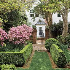 Beauty Takes Flight | Wing Haven | SouthernLiving.com    Love the formal boxwood hedge and the pop of pink.  Very 'secret garden-ish'