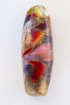 Multi pieces of glass called frit are incorporated on to the mandrel. #glassbeads