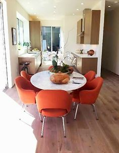 COCOCOZY: HOLLYWOOD HILLS WITH A VIEW - WEEKEND HOUSE TOUR - Dining room with orange Eames Chairs and Saarinen oval Tulip table.  Open kitchen modern home