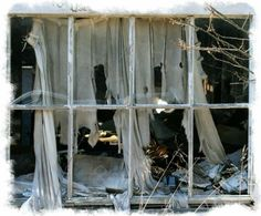 a tattered old curtain hangs through the broken panes of glass in this abandoned old house.