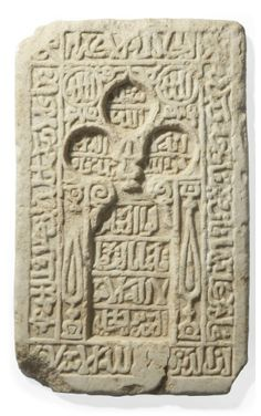 A GHAZNAVID MARBLE MIHRAB TILE   AFGHANISTAN, 11TH/12TH CENTURY   Of rectangular form, carved with a central niche with trefoiled arch, a stylized mosque lamp hanging from the arch, the columns at either side with stylized cypress trees, bordered with inscriptions in naskh script from Qur'an III (sura al 'imran), v.18 and Qur'an LV (sura al-rahman)