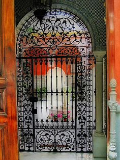 photo ... entrance to a house in Sevilla, Spain ... example of ironwork  ... looking in to the patio ...
