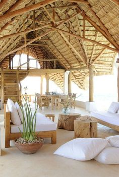 Tropical home with a thatched roof and simple wood furniture