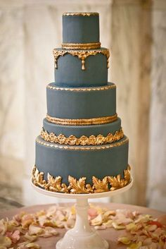 A beautiful, ornate dusk blue and gold wedding cake
