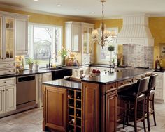 A farmhouse kitchen is designed for the baker of the home with wrap around cabinetry and an exquisite island with prep space and sink.