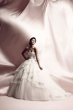 Glory - Off White Italian Lace and Tulle sweetheart strapless ball gown with asymmetrical multi layered skirt and floral appliques with a beaded belt at natural waist.