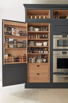 A smartly designed pantry sits at either side of this kitchen featuring shelves, racks and storage for dried goods, condiments and spices. Seamlessly hidden behind dark grey doors are deep drawers for kitchen essentials making sure everyday items are out of sight but within easy reach.