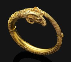 An antique Byzantine revival gold bangle, of hinged design and oriental inspiration, the textured gold ram's head terminal to the highly decorated band of bead and rope-twist detail.