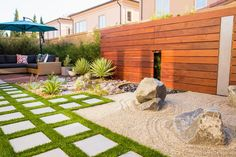 Clean geometry and simple succulent plantings combine with a rock garden and water feature in this restful, modern zen backyard. A large shade forms a comfortable resting spot in one corner.
