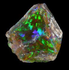 No. 44831 Mineral:Opal (var. Crystal Fire Opal) Locality:570 km north of Addis Ababa, Wello (Wollo), Delanta Plateau, Tigray, Ethiopia. Transparent fire opal rough with conchoidal surfaces revealing intense green, blue, and orange internal flashes of color. Must be seen to be appreciated. This new find is also called Crystal Opal because it is transparent and as hard as Brazilian opal. Total weight 88.5 carats Overall Size:30x25x20 mm