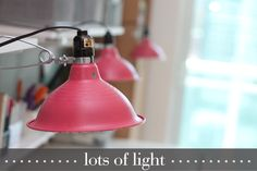 "craft room lighting by Damask Love:  clamp work lights ($8.50 each at Home Depot) + spray paint + Ecosmart 14 watt/60 watt equivalent ""daylight"" bulbs"