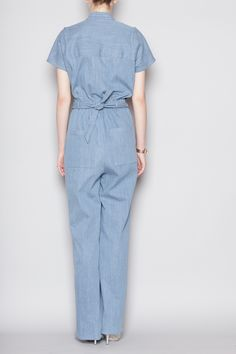 Short sleeve jumpsuit in a medium-weight denim fabric. Round neck with concealed front button closure. Elastic back waist with attached belt tie. Seam flat at shoulders. Side slit and rear pouch pockets. Slips on. Dry clean.