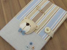 Porta Caderneta de Vacinas <br>Tema Urso <br>Tecido 100% algodão . Porta cadernetas com bolsinho para cartões na aba interna . <br> <br>Aplique de urso em feltro . Nome bordado a mão . <br> <br>Pode ser feito em outras temas , cores e estampas !! <br> <br>Ideal para Conservar e Organizar os documentos do Bebê com muito charme e estilo !!