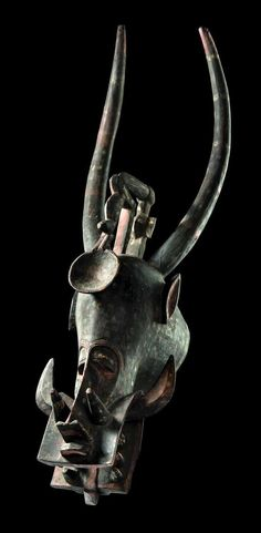Africa | 'Wanjugo' mask from the Senufo people of the Ivory Coast | Wood; dark brown patina, with remains of white and red pigment.  | The 'wanjugo' mask is worn by members of the 'wabele' society.
