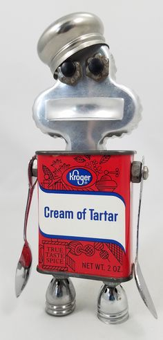 Carter Size: 7 inches tall Medium: Vintage Kroger Cream of Tartar Tin, Vintage Collector Spoons, Aluminum Cookie Cutter, Vintage Salt and Pepper Lids, Nuts, Bolts and Washers.