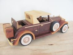 This is my 1931 Cadillac Roadster. The main body is Dark Walnut. The tiers are ebonized and the white walls are inlaid Holly. The whole model has a coat of Tung oil applied, there is no paint any where. Woodworking Projects For Kids, Woodworking Workshop, Diy Woodworking, Wooden Toy Cars, Wood Toys, Powered Wheelchair, Fishing Tackle Box, Pinewood Derby, Cadillac