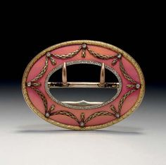 A Jeweled Two-Color Gold Mounted Guilloché Enamel Belt Buckle Marked Fabergé, workmaster's mark of Henrik Wigström, St. Petersburg, 1896-1908, scratched inventory number 15264 Oval, with gold palmate border, overall enameled in translucent pink over a wavy guilloché ground, with gold foliate garlands set at intervals with rose-cut diamonds, the inner border set with rose-cut diamonds, with double belt catch, fully marked.