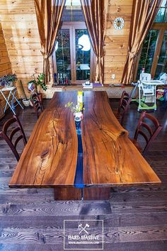 A large modern dining table made of solid wood with a live edge. Wood Karagach is very durable with a beautiful texture. Table in the River style from epoxy resin with a blue tint. The knots and natural cracks in the tree are also filled with resin. It looks very stylish! The size of