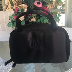 Saks Fifth Avenue black satin travel cosmetic case NWOT  This sleek travel case has three zipper compartments ready to stow loads of cosmetic essentials. Red lining adds a gorgeous pop of color. Saks Fifth Avenue Bags Cosmetic Bags & Cases