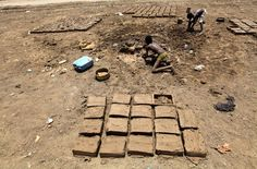 A boy from the Darfur region makes mud blocks in Khartoum, Sudan, on September 17, 2011. Many people in Darfur live in slums outside Khartoum and try to make a living by selling mud bricks or performing other small jobs.