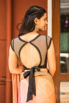 Ready to shop blouses House Of Blouse Calling dibs on this sizzling black number! In a shimmer net fabric to give you just the right amount of sparkle and a sheer lace edged tie back for some major sizzle. This little black blouse is right up there with Blouse Back Neck Designs, Netted Blouse Designs, Fancy Blouse Designs, Saree Blouse Designs, Blouse Styles, Blouse Patterns, Blouse Designs Catalogue, Saris, House Of Blouse