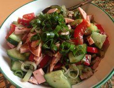Für den bunten Wurstsalat mit Kernöl zuerst das Gemüse klein schneiden, die Zwiebel in feine Ringe und die Wurst in passende Stücke. Mit dem