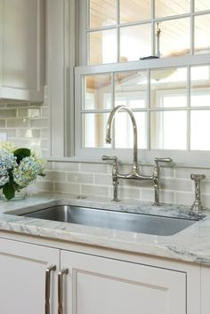 Taupey gray subway tiles with white grout - adds texture to an all white kitchen