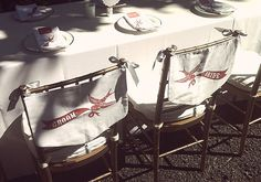 DIY Chair Backs For the Bride and Groom!: Fabric bibs were stamped to match the wedding theme and marked the bride's and groom's seats.  Source: Anne Nunn Photography via 100 Layer Cake