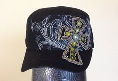 This black cadet cap features a grey screen printed pattern across the front of the hat, along with grey embroidery that follows the pattern. There is a black fabric cross embellished with metallic and green patterned beading that covers part of the front and bill of the cap.  - Three-panel construction. - Embroidered design. - Screen printed design. - Patterned and metallic beads. - Adjustable closure at back. - 100% Cotton.