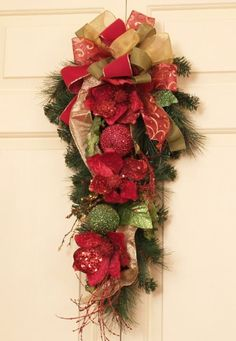 """Our exclusive 36"""" Holiday Door Piece is a lovely mixture of the holiday colors. The magnolias and fruit are nestled on a lush pine base with a beautiful mixed coordinating ribbon bow."""